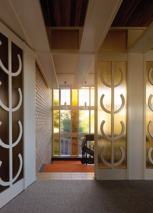 "A glass screen at the top of the entry stair displays the ""house motif"" – a series of abstracted candelabras."