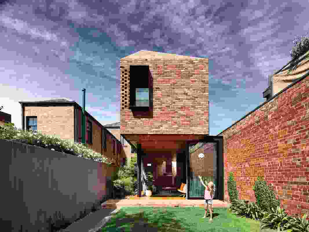 The red bricks of the extension angle up to become a roof, giving cohesion and simplicity to the built form.