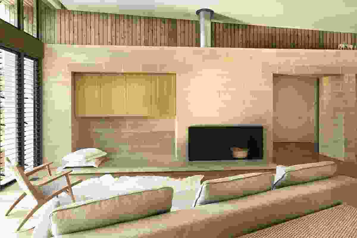 A concrete block wall with a fireplace and niches for built-in furniture.