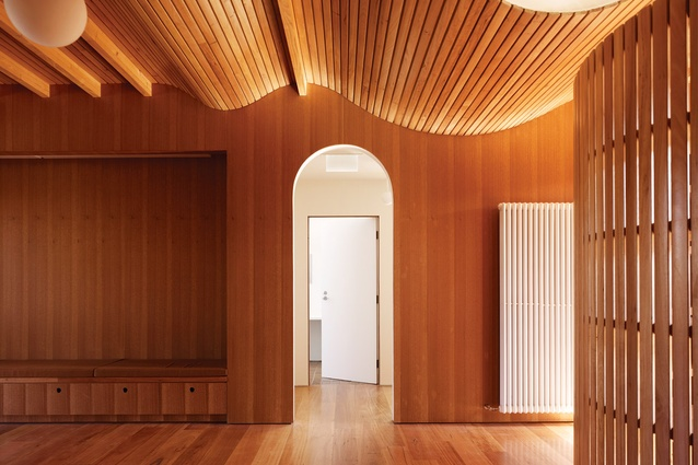 Naturally finished timber clads the central kitchen and learning space, including the battened screen and undulating ceiling.