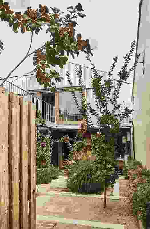 The L-shaped plan allows half the street frontage to be filled by a verdant courtyard garden.