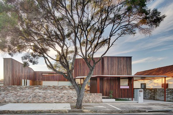 The house is a U-shape around a front courtyard hidden behind a modest brick wall.