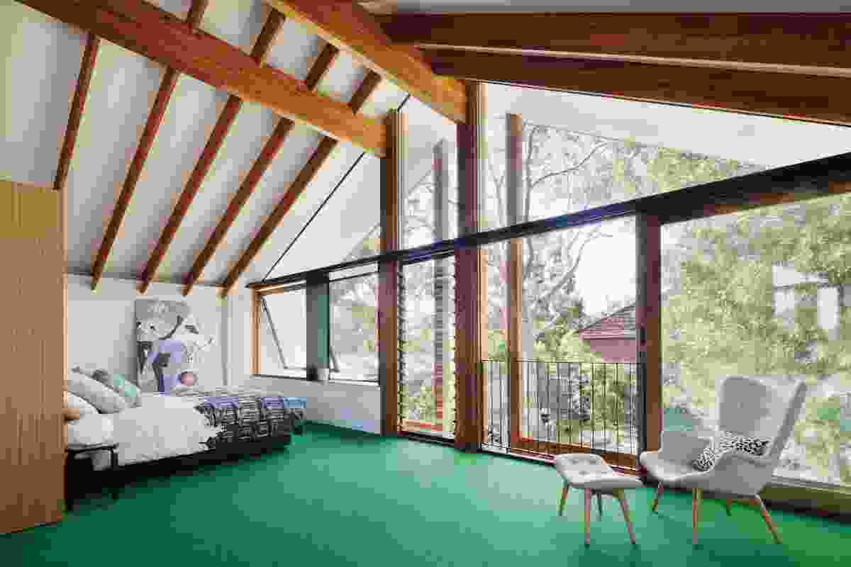 The light and airy bedroom suite on the first floor sits among the treetops, with the carefully detailed carpentry of the pitched roof exposed. Artwork: Helen Johnson.