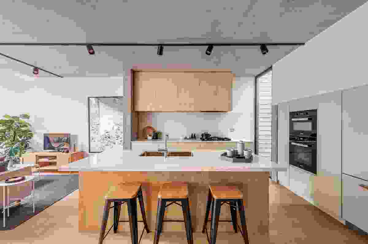 Stone and timber are used on inset kitchen joinery and the central island bench, delineating this space from the main living zone.