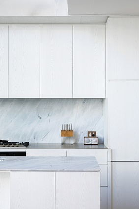 White cabinetry and marble-tiled benchtops contribute to a sharp yet warm palette in the kitchen.