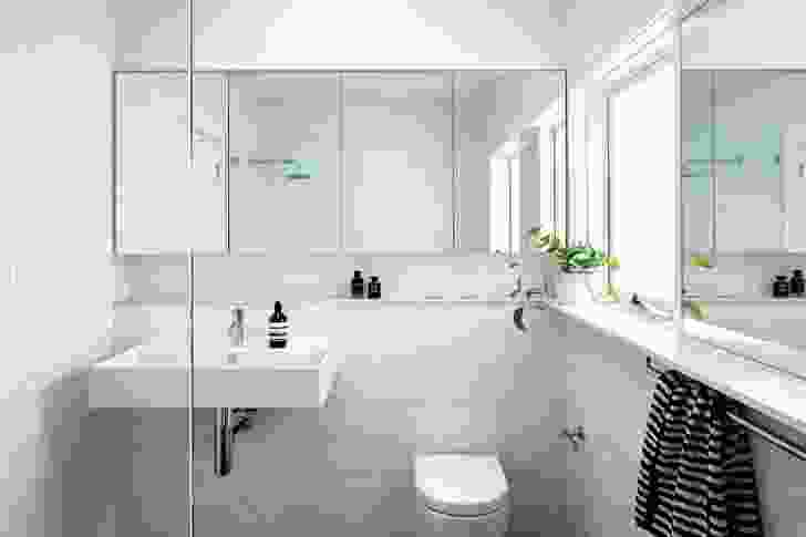 The bathroom's minimalist aesthetic is emphasized by an all-white palette.