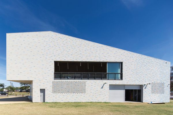 The striking and monolithic form of the north elevation is punctured only by a long balcony, garage doors and breezeblock screens on the lower level.