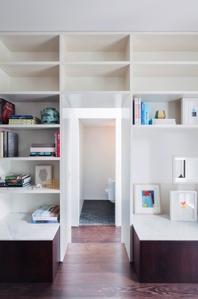 Deep joinery units provide ample storage at the connection between the living room and the hallway.