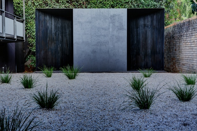Timber exterior blackened by fire, steel perforated by water.