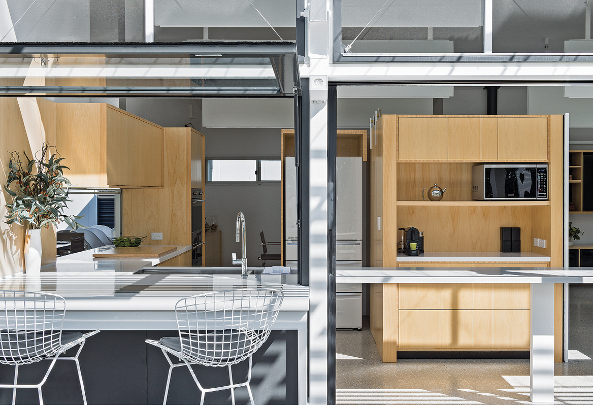 The home consists of two steel-framed pavilions: one, a double-heighted space, unites kitchen, dining and living areas and extends to the deep verandah.