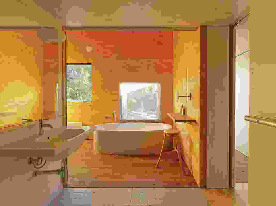 A room is dedicated to the act of bathing. An opening allows connection to the outdoors via a flyscreen.