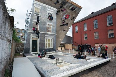Reflections from a large mirror in Dalston House create the illusion that people are hanging off a real facade.