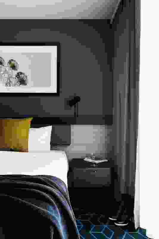 In the guest rooms, the materials palette adds textured wallpaper and timber elements to the familiar black steel fixtures and custom-patterned carpet seen elsewhere in the hotel. Artwork: Jeremy Blincoe.