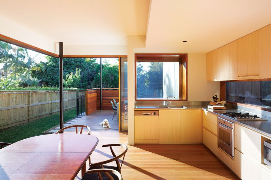 The glazed walls of the kitchen peel away to form a carved-out shell of wall and roof.