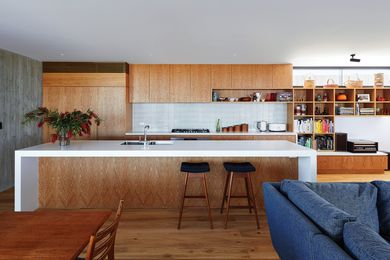 Crisp lines and oak joinery soften the exposed concrete of the northern wall.