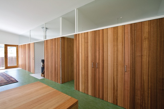 Timber panelled doors and walls hide rooms and storage.