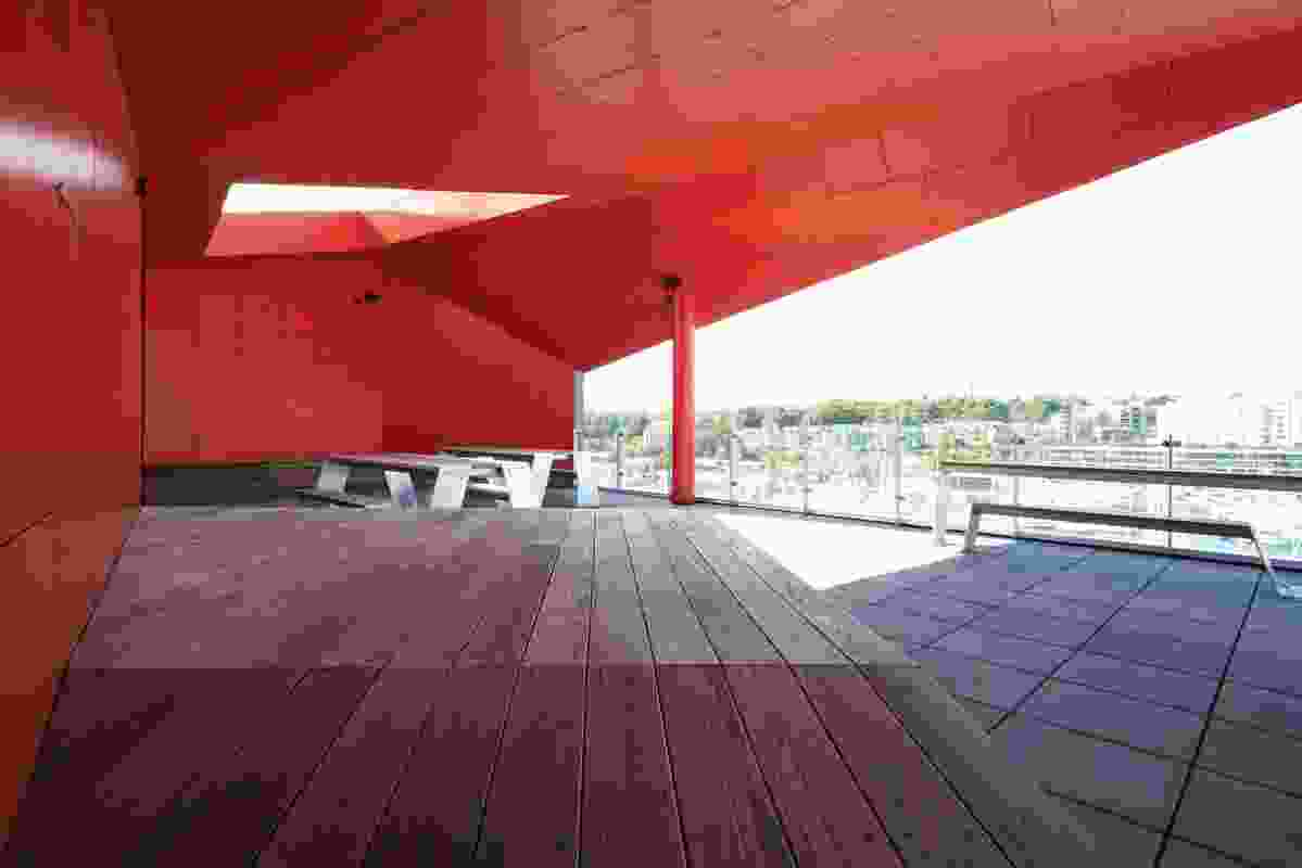 Four large, colourful openings in the building's monolithic volume include the two rooftop terraces, clad in vibrant red panels.