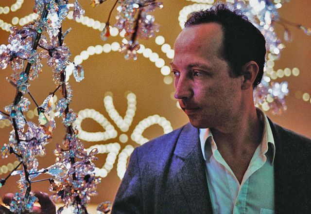 Tord Boontje with his chandelier designed for Swarovski, Blossom.
