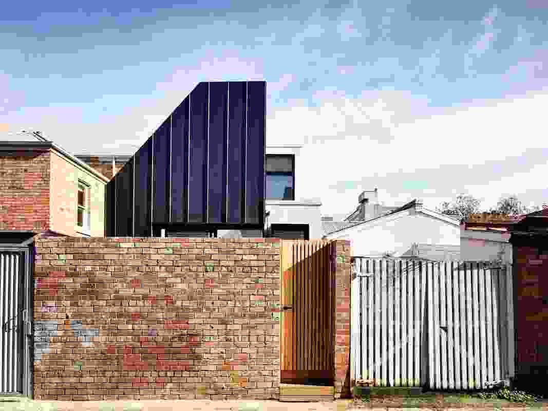 The new eastern facade is clad in dark zinc panels and is set back from the laneway boundary to allow for a small courtyard.