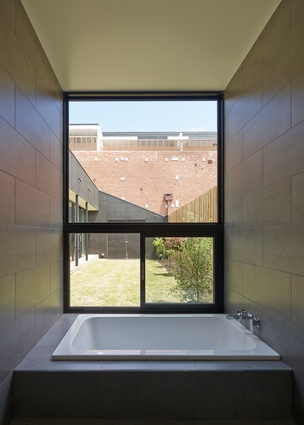 A large window is adjacent to the bath to give the feeling of bathing outside.
