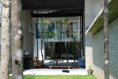 Gardenshell house – the shell of its living room helping to shield from the elevated mass transit rail to the rear, while making a pavilion of its living room between front garden and middle courtyard