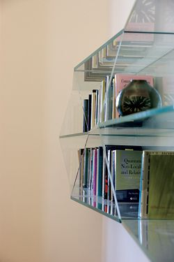 Detail of the triangulated structural glass bookshelf, carefully pinned to the wall.