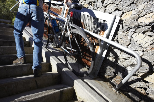 The steep gradient ruled out ramp access so the staircase incorporates a groove on its edge to make transporting bikes easier.