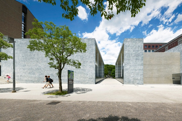 The two separate volumes visually read as a single building, in part due to the consistent and distinctive material choice of cut grey hand-finished tiles.