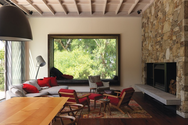 Framed in salvaged wandoo, a picture window gazes into the treetops from the main living space.