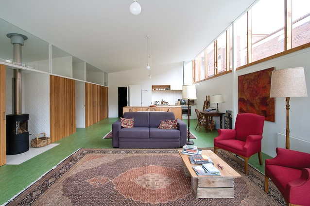 Located to the rear of the shopfront, the residence is one large living room defined by white walls, solid timber panelling and green linoleum.
