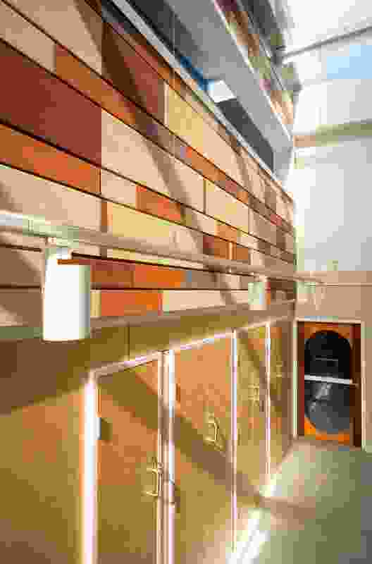 Terracotta tiles of varied sizes create a brick bond-style pattern, referencing the heritage brickwork of the substation itself.
