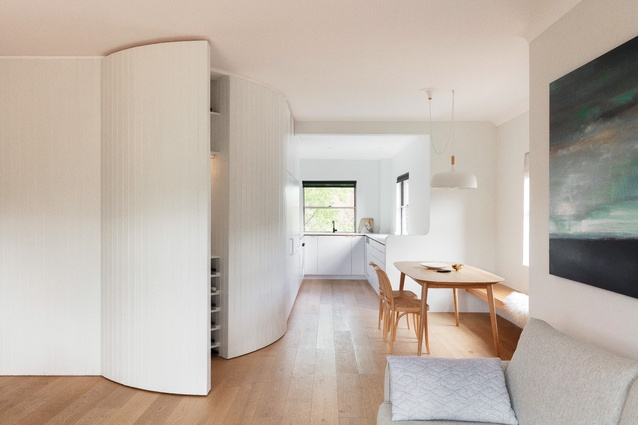 The insertion of a curved timber-panelled joinery wall defines the zones within the apartment, conceals original splayed walls and provides storage space. Artwork: unknown artist.