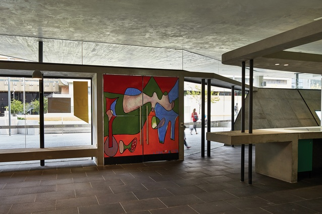 Handpainted entry doors, a homage to Le Corbusier, are an expressive contrast to the concrete material palette.