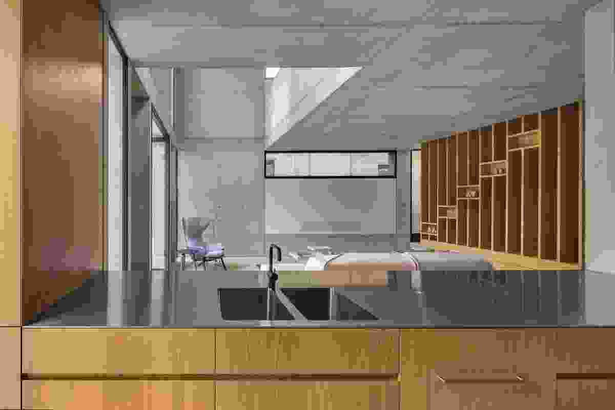 The kitchen sits on one side of the new, rear living space, with a double-height void above the sitting area.