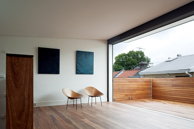 The upper-level living space opens up to a balcony.