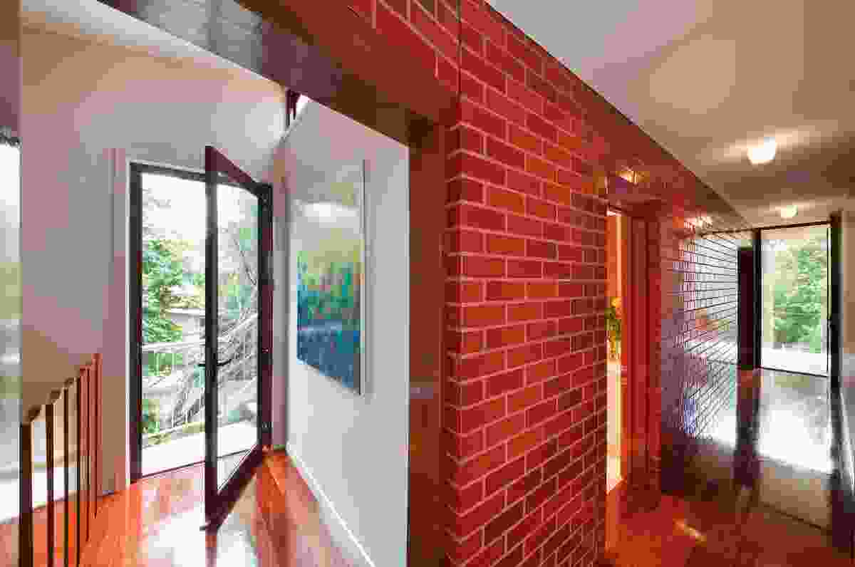 Bedroom spaces are organized within the red brick blade walls.