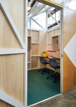 The pods feature built-in desks and open shelving. Their open-top, saw-tooth roofs are clad in polycarbonate sheeting to expose the timber framework beneath.