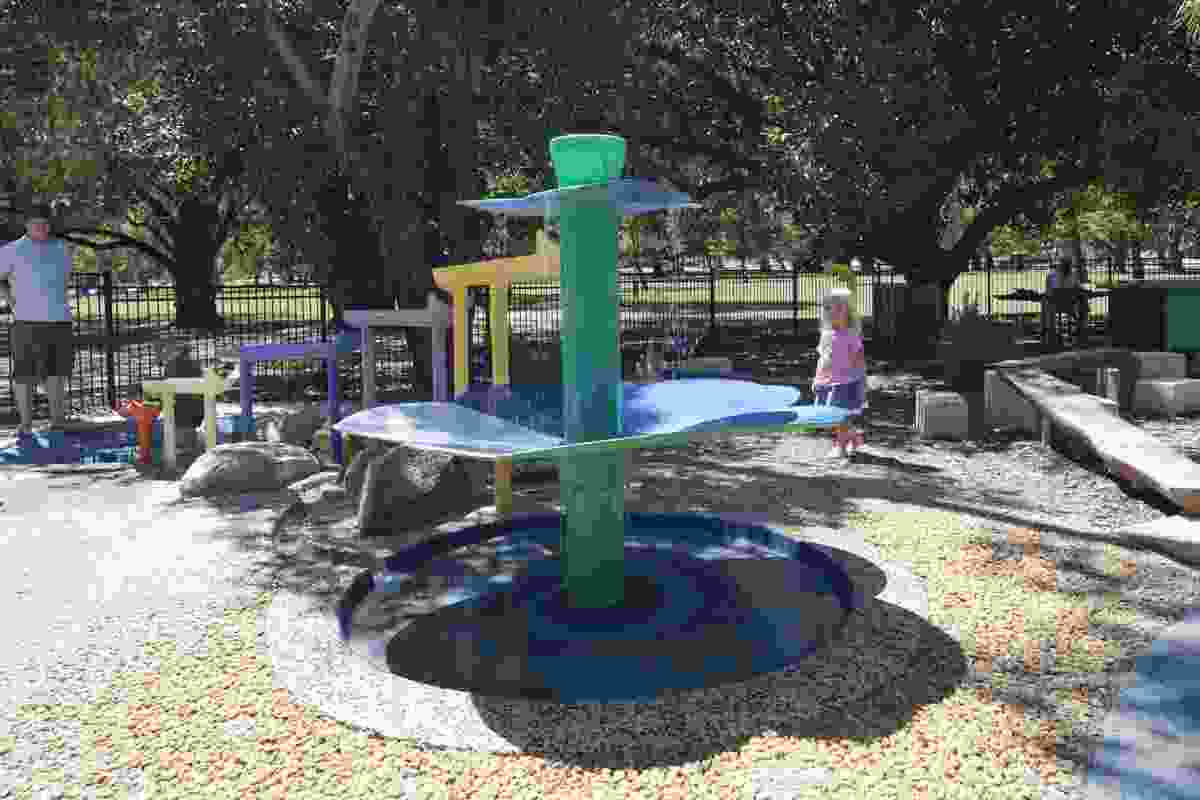 Water spills from the flower fountain, adding the sound of running water to the noise of the playspace.
