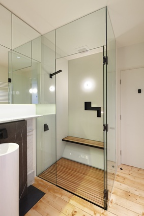 Minimal glazed shower with timber floors and bench seating.