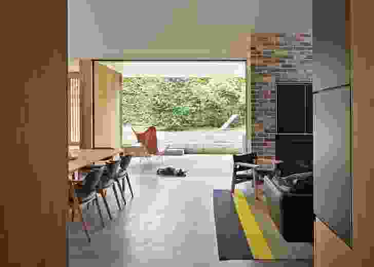 An expansive covered outdoor area sits between the wide rear garden and the living area.