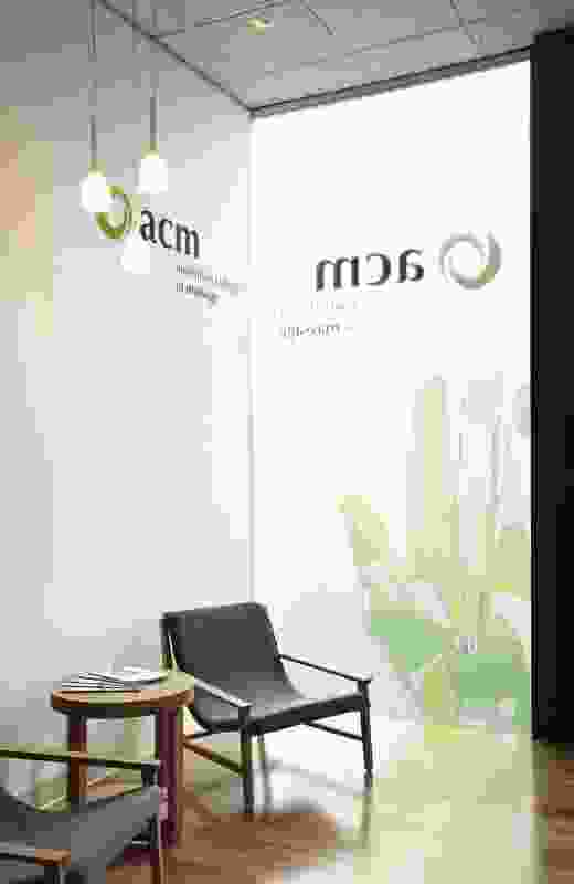 Waiting chairs and table by Temperature Design in neutral colours with signature graphics behind.