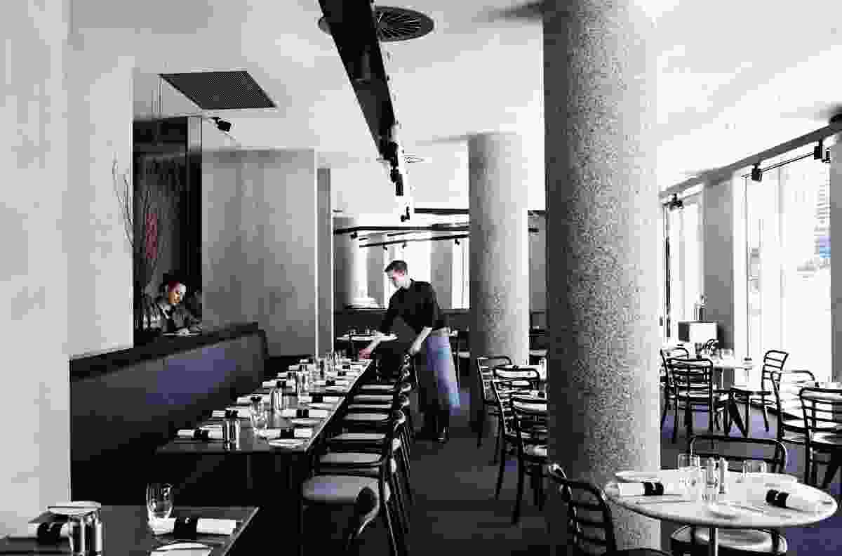 Plush upholstered banquettes soften the exposed concrete walls.