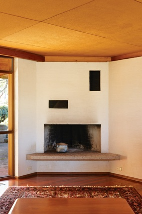 A large corner fireplace dominates the sitting end of the living room.