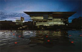Queensland Gallery of Modern Art. The winning architects, Architectus and Davenport Campbell, proposed a loose connection between strategy and form. The artwork shown in the section is Family Tree by Zhang Huan, 2000. The river view by night includes images of Saint Sebastian by Fiona Tan, 2001, and River Time in the River by