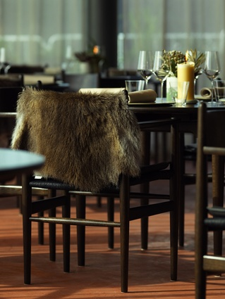 Wallaby pelts are placed on the dining chairs.