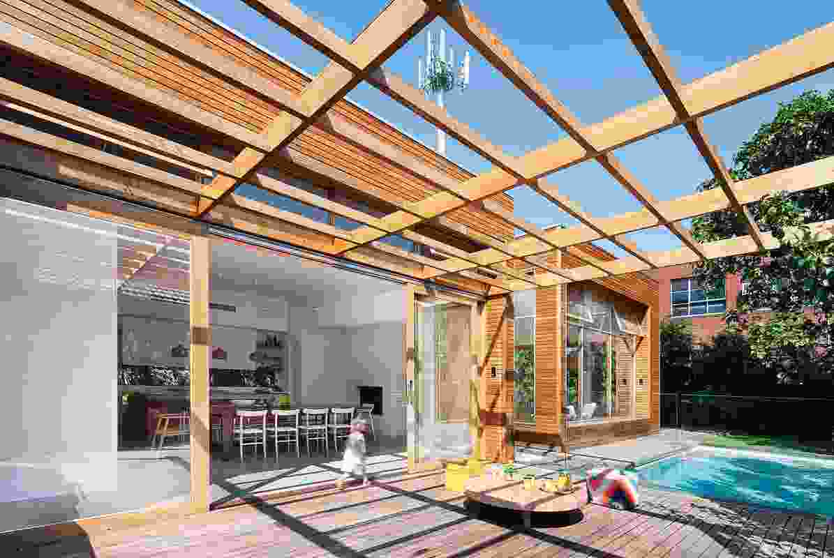The pool deck sits under a timber pergola that resembles a deconstructed version of the timber-clad pavilion.