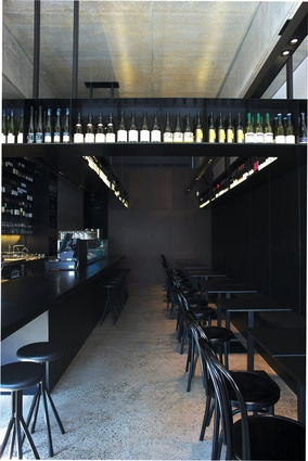 An overhanging display shelf suspends bottles of wine above the dining area.