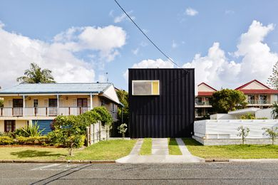When viewed from the street, the house appears as a dark box clad in compressed fibre cement sheeting and striped with battens.