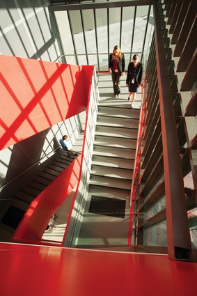 Circulation at the western end of the building is defined by a red-orange ribbon, which links stair to entry.