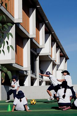 N°13 The active playground, with the concrete fins and timber detailing of the western facade beyond.